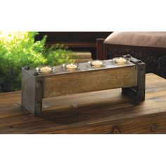 Distressed Wooden Tealight Candle Holder - Contemporary, chic and fascinating, this Distressed Wooden Tealight Candle Holder makes a style statement that won't be ignored. Four glass candle cups rest inside a distressed wooden block that's framed with metal ends complete with bolt accents. This mod lighting accent will turn candlelight into contemporary glow!