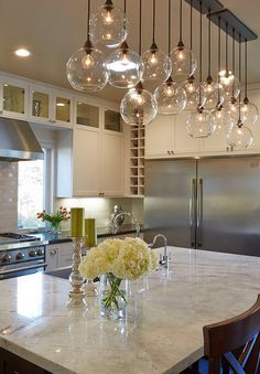Stunning kitchen with a modern, yet cozy feel. Glamorous, yet industrial. The pendant lighting is my favorite part.