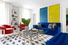 Blue tufted sofa with large-scale colorful art and red lounge chairs.