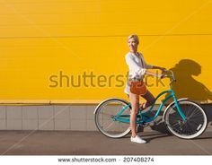 Young sexy blonde girl is standing near the vintage green bicycle with brown…