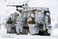 Royal Marines of Whiskey Company, 45 Cdo deploy from a   Viking armoured personnel vehicle armed with a .50 cal machine gun, during a live firing exercise in Norway, as part of their Winter Deployment.