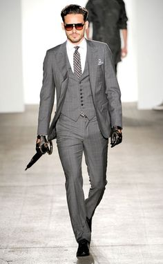 A grey men's three piece suit from Simon Spurr. Note the peak lapels and flourish to the peak handkerchief.