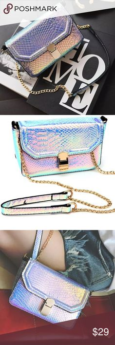 Chloe Silver Metallic Mini Crossbody Handbag NWT. Boutique item. Just in! The hologram vegan leather handbag features a holographic silhouette.  The stylish versatile bag can be used as a cross body, clutch,shoulder bag. Metallic snake skin like fabric with a gold chain shoulder strap lining, gold hardware and one inside non zip pocket. Height Measurements: 7x4.5x2.5. Shoulder Strap: Not Adjustable, but detachable to covert into a clutch. ShopPave Bags Crossbody Bags