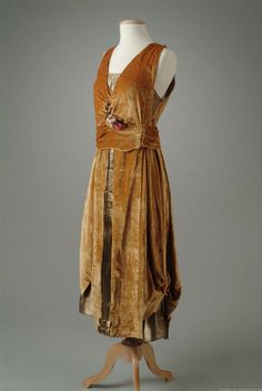 c. 1921. Old-gold velvet evening gown with a bodice, under-skirt and front panels of gold lame. The overall skirt is caught up at the sides with velvet cording and gold bullion tassels to create an eighteenth century effect. Details include a small accent of metallic flowers at the wasit.