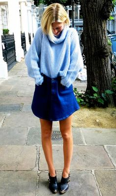 Pandora Sykes wears a denim skirt with an oversized blue sweater and booties