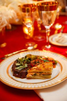 An entree of petite filet of beef accompanied by potato lasagna and juilenne vegetables.