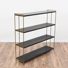 This mid century modern bookshelf is featured in a wood with a simple black paint finish. This bookcase is in great condition with 4 tier shelves, durable metal sides in a shiny brass and a sleek modern design. Simple display case perfect for books and knick knacks! #midcenturymodern #storage #bookcase&shelving #sandiegovintage #vintagefurniture