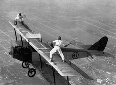 Daredevils playing tennis on flying biplane's wings