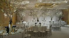 white wedding: white carpeted ballroom, mirrored tables with centerpieces of soaring dogwood branches flanked by crystal candlesticks and vases of purple anemone