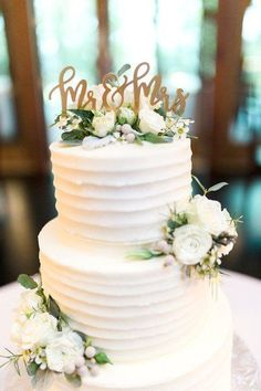 """Spring Tennessee Chapel Wedding Classic wedding cake idea – two-tier, buttercream-frosted wedding cake with greenery and white flowers and gold """"Mr & Mrs. Floral Wedding Cakes, Elegant Wedding Cakes, Wedding Cakes With Flowers, Wedding Cake Designs, Wedding Cake With Topper, Wedding Cake Two Tier, Wedding Cake Frosting, White And Gold Wedding Cake, Two Tier Cake"""