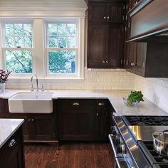 This is similar to the dark color cabinets and light color counter I want in our Kitchen. Debating between a white farmhouse sink and a stainless undermount
