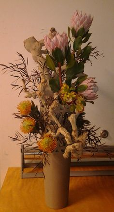 Pin cushion protea, orchids, protea with greenery and grape wood. Corsage And Boutonniere, Pin Cushions, Event Design, Custom Homes, Greenery, Orchids, Floral Design, Tropical, Wood