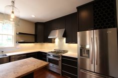 Check out the cool glass backsplash paired with dark contrasting cabinets. Give this kitchen a dramatic flair!