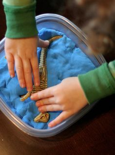 """After kids unearth the dinosaur skeletons provided in the Dino Dig Party in a Box, let them make """"fossils"""" in a container of clay.  Partezy.com"""