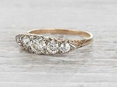 Vintage Victorian half hoop ring made in 14k yellow gold and silver. Centered with an approximately .71 carat EGL certified old European cut diamond with H-I color and SI2 clarity. Accented with four old European cut diamonds weighing approximately .60 carats total. Circa 1890. Gold carved rings were popular during the Victorian era. This stunner can be worn as a wedding band, or stacked alongside other rings for an equally spectacular look. Diamond and gold mining has caused devastation in…