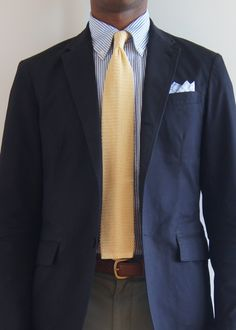 Navy sport coat, white shirt with light blue dress stripes, yellow knit tie, olive pants