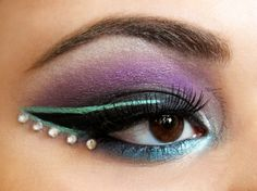 Dramatically lined purple, teal and aqua eye shadow with a row of crystal accents.