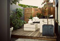 www.buytengewoon.nl. tuinontwerp - tuinaanleg - tuinonderhoud.  Kleine mini-achtertuin van 45 m2 in Elspeet. De grijs-, wit- en groentinten vormen een mooie compositie. Met kleine veranda en kunstgras met tuindouche voor de kinderen. www.buytengewoon.nl