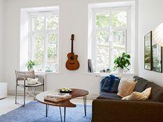 Wohnzimmer mit Coachtisch in Nierenform und jeansfarbigem Teppich.