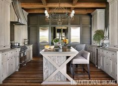 Fine craftsmanship prevails in this kitchen with its custom-made cabinets and reclaimed wood floors. - Traditional Home ® / Photo: Emily Jenkins Followill / Design: Susan Ferrier