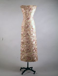 Pink and White Lace Dress Designer: Oleg Cassini (American, b. France 1913-2006) Date Made: 1961 Medium: Raffia lace Evening dress in pink-and-white raffia lace with matching kerchief stole.  Fabric has scalloped edge at hem, neckline and arm holes.  Dress is fitted at waist and falls straight to the heel. This dress was worn by Jacqueline Kennedy arriving at a dinner given by President and Madame Charles de Gaulle at the Elysée Palace, France on May 31, 1961.