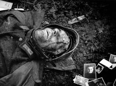 A dead German soldier killed during the Battle of the Bulge is seen surrounded by family photographs, Hürtgen Forest, GER/December 1944