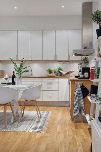 un apartamento nrdico con mucho estilo una cocina blanca un sof gris y el