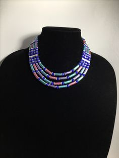 Handmade four-strand hand painted paper bead necklace accented with metal and glass beads.