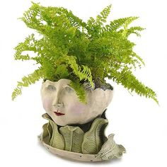 "Handcrafted Victorian Lovelies Planter - Flaunting Flora Version. Victorian Lovelies are indoor planters meticulously hand-sculpted with a charismatic presence! Flaunting Flora boasts a collar of large carved leaves and features an inviting smile, blush cheeks, and bird's nest accent. The finish is completely fired and water safe. The planter is approximately 5"" wide x 3"" deep, perfect for small indoor plants. Each planter is handcrafted making each sculpture truly unique!"