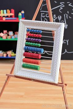 """DIY abacus. 1) Paint an open frame, dowel rods and wooden beads and wheels. Let dry. 3) Cut 4, 12"""" pieces of a 3/16"""" and 1/8"""" dowel rod. 4) Using 1/8"""" drill bit, drill 8 holes (4 on each side directly across) being sure to evenly space the holes. 5) Do the same for the other 8 holes, only with 3/16"""" drill bit. 6) Slide all beads (by color) onto the 3/16"""" dowel rods and all wheels onto the 1/8"""" dowel rods. 7) Push the ends of all dowel rods into the appropriate holes. Use glue to secure."""