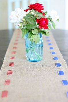 We are loving the rustic look of this patriotic table runner, and it couldn't be simpler to make! The striped red and and blue ribbon with the natural burlap creates a look that's appropriate for the 4th of July, but still usable on other occasions. And since the ribbon is simply woven through the slits, there's no sewing required. In fact, we're picturing swapping out the ribbon for other occasions—perhaps a sparkly white ribbon for Christmas?