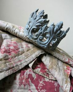 Brocante find, a zinc crown on an old quilt .