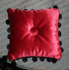 small velvet cushion with button and bobble trim
