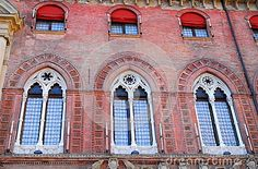 Photo made at the municipal building Accursio or located in Piazza Maggiore in Bologna in Emilia Romagna (Italy). In the image, which takes up a portion of the facade of the building, you see three beautiful mullioned windows decorated with white stone. There are many over the mullioned windows with red curtains fire raised in half.