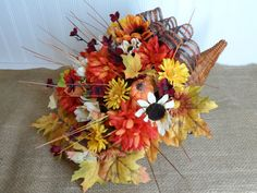 Large Cornucopia Basket, known as the Horn of Plenty. Decorate your Thanksgiving table with one of my beautiful cornucopia baskets. These cornucopia baskets look so festive on your dining room table and depict the traditional Thanksgiving holiday. I have been making cornucopia baskets for over 25 years. This is one of my most popular items during the Thanksgiving season.  The basket is filled with Fall flowers and greenery and is strong and of good quality. Styrofoam fills the bottom which…