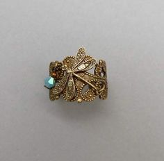 """Ornate   Dragonfly Ring  An antiqued brass """"cigar band"""" style ring is layered with a tiny dragonfly and a tiny turquoise Swarovski crystal dangle. Ring is adjustable.    Item #R100 - $32.00"""