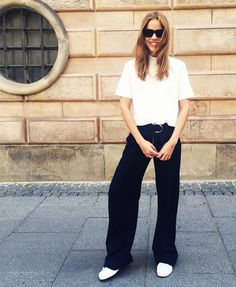 A high neck white short sleeve top is worn with black wide-leg trousers, white tennis shoes, a belt and sunglasses.