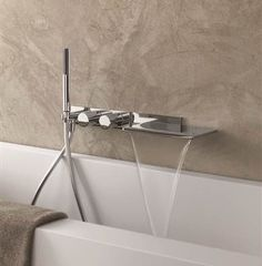 Franco Sargiani's luxury Milano Collection for Fantini offers a sleek chrome accent to the modern and contemporary bathtub in the bathroom space.