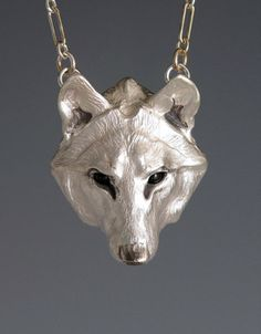 Materials: Cast sterling silver, Onyx eyes, 20-inch sterling silver link chain.Description: lightweight hollow silver form lined w/ synthetic leather.Wolf head: 1 5/8 inch length.