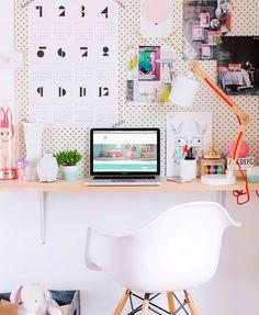 Decoração de apartamento pequeno, mini apartamento, home office, escritório em casa, com pegboard, paredes brancas, cadeira branca e mesa de madeira.