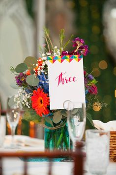 Colorful floral center pieces with colorful wedding table number Wedding Reception Centerpieces, Wedding Table Numbers, Floral Centerpieces, Floral Arrangements, Whimsical Wedding Theme, Floral Wedding, Wedding Colors, Rooftop Wedding, Center Pieces