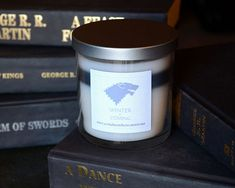 House Stark - Winter is Coming  Enjoy this natural soy candle in the colors of House Stark of Winterfell. Inspired by HBOs series Game of Thrones and George R.R. Martins book series, A Song of Ice and Fire. The 11.5 oz layered candle features a label with the house sigil and house words, and a flat, silver lid. Smells like fir trees and cold winter air.  *Custom scents available. Can also be left unscented upon request.