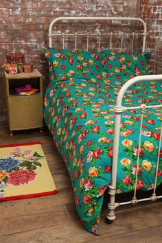 Floral duvet and antique kid's bed with exposed brick wall. Very gypsylike