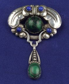 Sterling Silver, Malachite and Lapis Brooch, Kay Bojesen, set with malachite and lapis cabochons within a stylized foliate frame with flexible pendant, maker's mark. Note: Bojesen was an apprentice in the Jensen workshop.