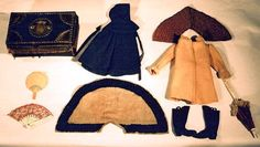 """77. Doll clothing: 19th c. leather brass beaded trunk, 10"""" l, marbleized paper interior, carved round wood fan, painted silk fan, Shaker type cloak, wool collar, quilted cotton collar, beige wool coat, 11"""" l, """"Candee"""" rubber boots, and carved ivory and red silk lace trimmed parasol, 10"""" l. $345"""