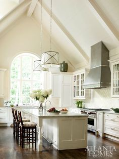 McLean tapped kitchen designer Laurie Lehrich for this voluminous space. Given the room's grand proportions, Lehrich extended the range hood up into the vaulted ceiling. Baker clad the ceiling in shiplap to achieve a relaxed, informal look. The cabinetry is by Design Galleria Kitchen and Bath Studio. Stools, Holland & Company. Light fixtures, Circa Lighting.