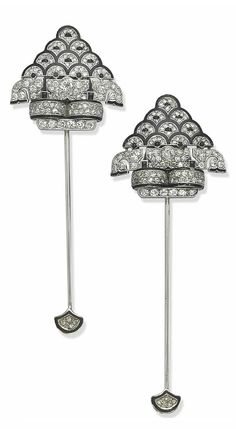 A PAIR OF ART DECO ONYX, ENAMEL AND DIAMOND JABOT PINS   Each detachable clip of shield shape, pavé-set with diamonds, enhanced with black enamel scalloped motifs and cabochon onyxes, the pin with enamel and diamond terminal, circa 1925, 9.0 cm (3.0 cm for the clips only)