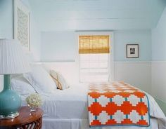 blue walls/ceiling and a pop of color in the bed spread