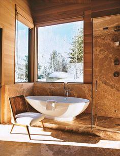 Rift-cut white-oak walls meet cedar marble in a bathroom. Mountain cabin living