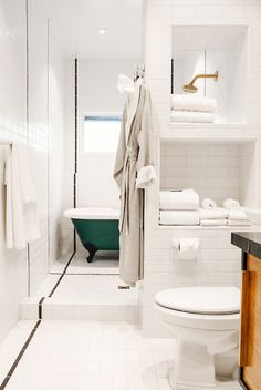 White bathroom with green tub and stacked towels